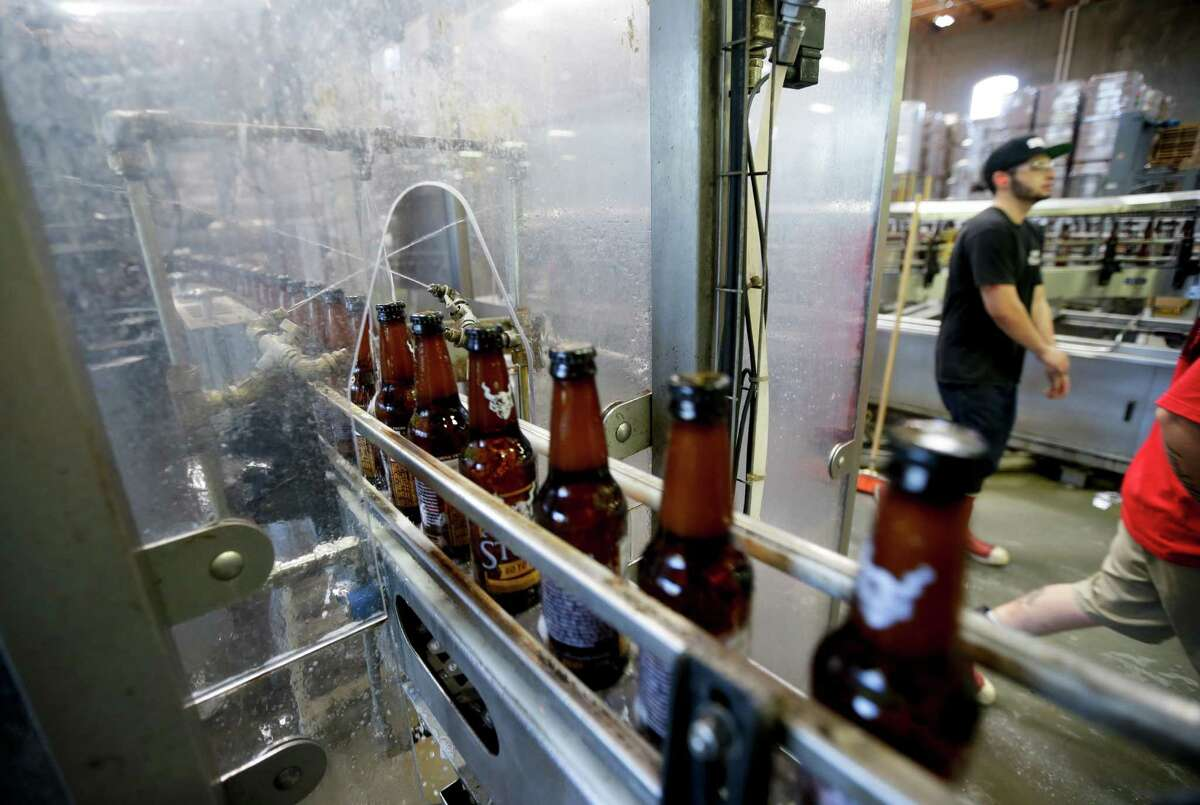 Bottles of beer are cleaned using recycled non-potable water during the bottling process at Stone Brewing Co. on Wednesday, Sept. 30, 2015, in Escondido, Calif. In an effort to reduce water use, the brewery is spending $1 million on expanding its $8 million wastewater treatment system installed in 2008, and aims to use only three gallons of water for every gallon of beer it produces. The treated water is used to clean equipment.