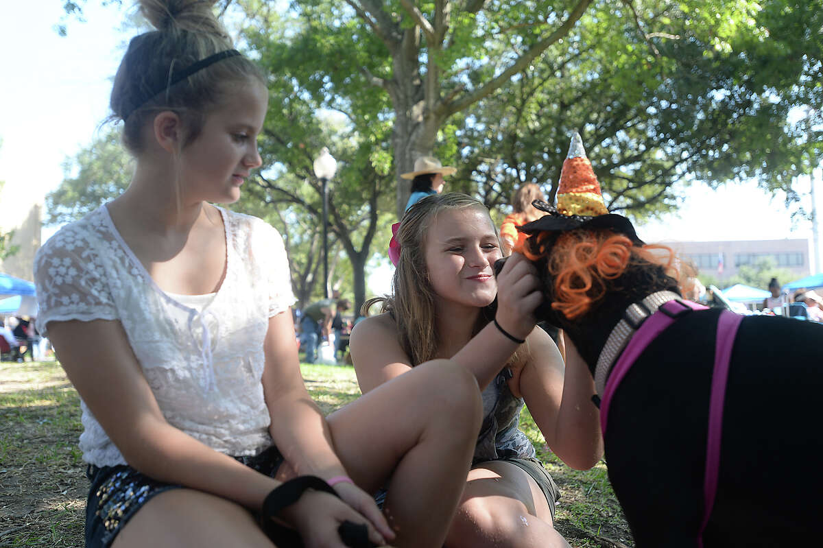 Dakota Young, 10, (left) looks on as friend Zoey Ivey, 10, shares a moment with her dog Malley during the annual Dogtoberfest event in Beaumont Saturday. Dogs and owners dress up and strut their stuff on a red carpet runway as they vie for a variety of titles and prizes. The event is hosted by Beaumont Main Street, a non-profit downtown development organization. Photo taken Saturday, October 10, 2015 Kim Brent/The Enterprise