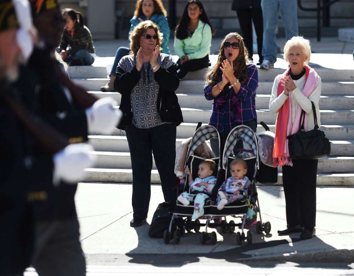 Jean Vaccaro, left, Rebecca Vaccaro-Jones, center, Jean Velanzon, right, and 1-year-old twins Lorelei and Matthew Jones, watch the festivities at the annual Columbus Day parade in Stamford, Conn. Sunday, Oct. 11, 2015. The event, led by Grand Marshal Genaro Rubino, paid tribute to Christopher Columbus and other great Italian explorers with a variety of bands, floats and local organizations marching.