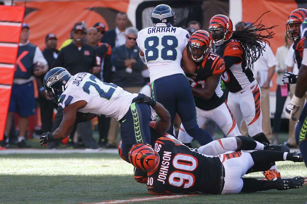 Seattle Seahawks running back Fred Jackson (22) is tackled by Cincinnati Bengals defensive end Michael Johnson (90) in overtime of an NFL football game, Sunday, Oct. 11, 2015, in Cincinnati. The Bengals won 27-24. (AP Photo/John Minchillo)