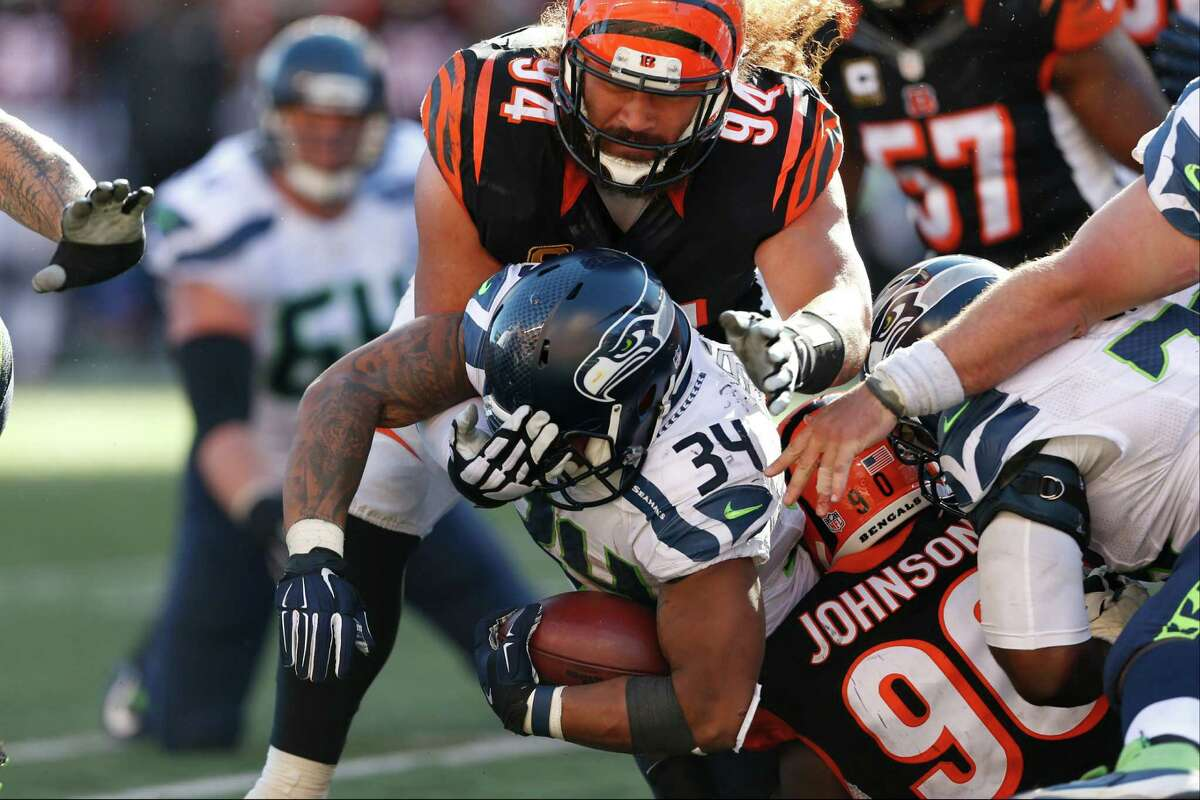Seattle Seahawks running back Thomas Rawls (34) is tackled by Cincinnati Bengals defensive end Michael Johnson (90) and defensive tackle Domata Peko (94) in overtime of an NFL football game, Sunday, Oct. 11, 2015, in Cincinnati. The Bengals won 27-24. (AP Photo/Gary Landers)