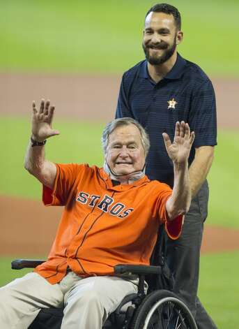 Former President George H.W. Bush waves before throwing out the ceremonial first pitch to Astros third baseman Jed Lowrie (8)before Game 3 of the American League Division Series against the Kansas City Royals at Minute Maid Park Sunday, Oct. 11, 2015, in Houston.  Photo: Brett Coomer, Houston Chronicle