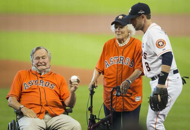Former President George H.W. Bush, with former First Lady Barbara Bush, holds a baseball after throwing out the ceremonial first pitch to Astros third baseman Jed Lowrie (8)before Game 3 of the American League Division Series against the Kansas City Royals at Minute Maid Park Sunday, Oct. 11, 2015, in Houston.  Photo: Melissa Phillip, Houston Chronicle