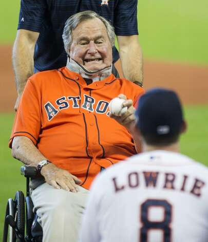 Former President George H.W. Bush throws out the ceremonial first pitch to Astros third baseman Jed Lowrie (8) before Game 3 of the American League Division Series against the Kansas City Royals at Minute Maid Park Sunday, Oct. 11, 2015, in Houston.  Photo: Brett Coomer, Houston Chronicle