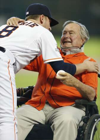 Former President George H.W. Bush embraces Astros third baseman Jed Lowrie (8) after throwing out the ceremonial first pitch before Game 3 of the American League Division Series against the Kansas City Royals at Minute Maid Park Sunday, Oct. 11, 2015, in Houston. Photo: Brett Coomer, Houston Chronicle