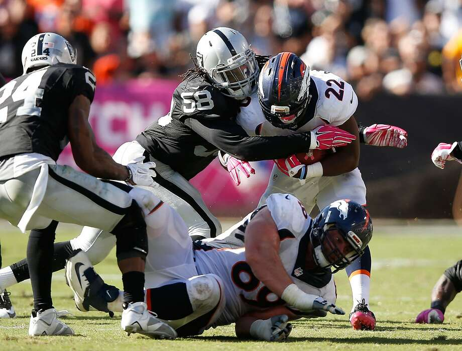Raiders linebacker Neiron Ball (58) puts the pressure on Denver RB C.J. Anderson (22) in the fourth quarter in a game the rookie played 36 snaps and shut down tight end Owen Daniels. Photo: Ezra Shaw, Getty Images