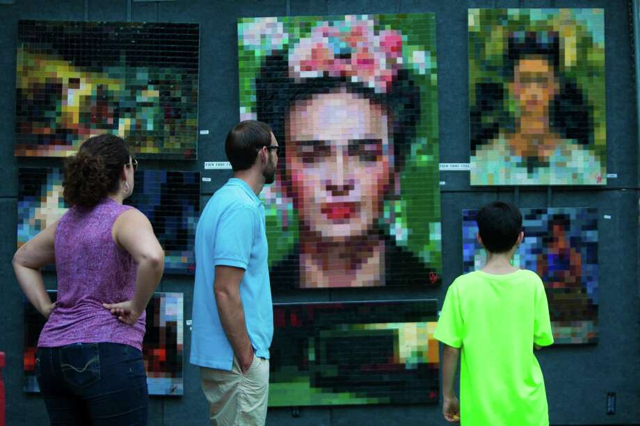 Visitors of the Bayou City Art Festival in downtown Houston admire a visual representation of the artist Frida Kahlo made out of mosaics, Sunday, Oct. 11, 2015, in Houston. ( Marie D. De Jesus / Houston Chronicle ) Photo: Marie D. De Jesus, Staff / © 2015 Houston Chronicle
