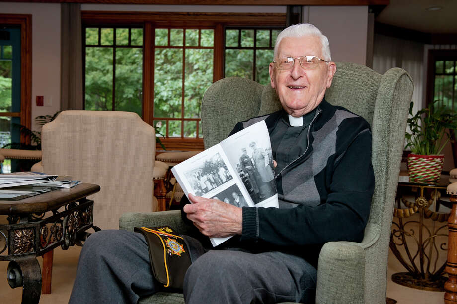 """Monsignor Thaddeus Malanowski, a 93-year-old Stamford native, flips to a photograph of Elvis Presley and himself pictured in his book while in his residence in Stamford, Conn. on Monday, Oct. 5, 2015. Malanowski rose to the rank of brigadier general, led chaplains in the U.S. Army, served as chaplain to Terry Schiavo and wrote a book, """"Sacrifice for God and Country."""" Photo: Amy Mortensen / For Hearst Connecticut Media / The Advocate"""