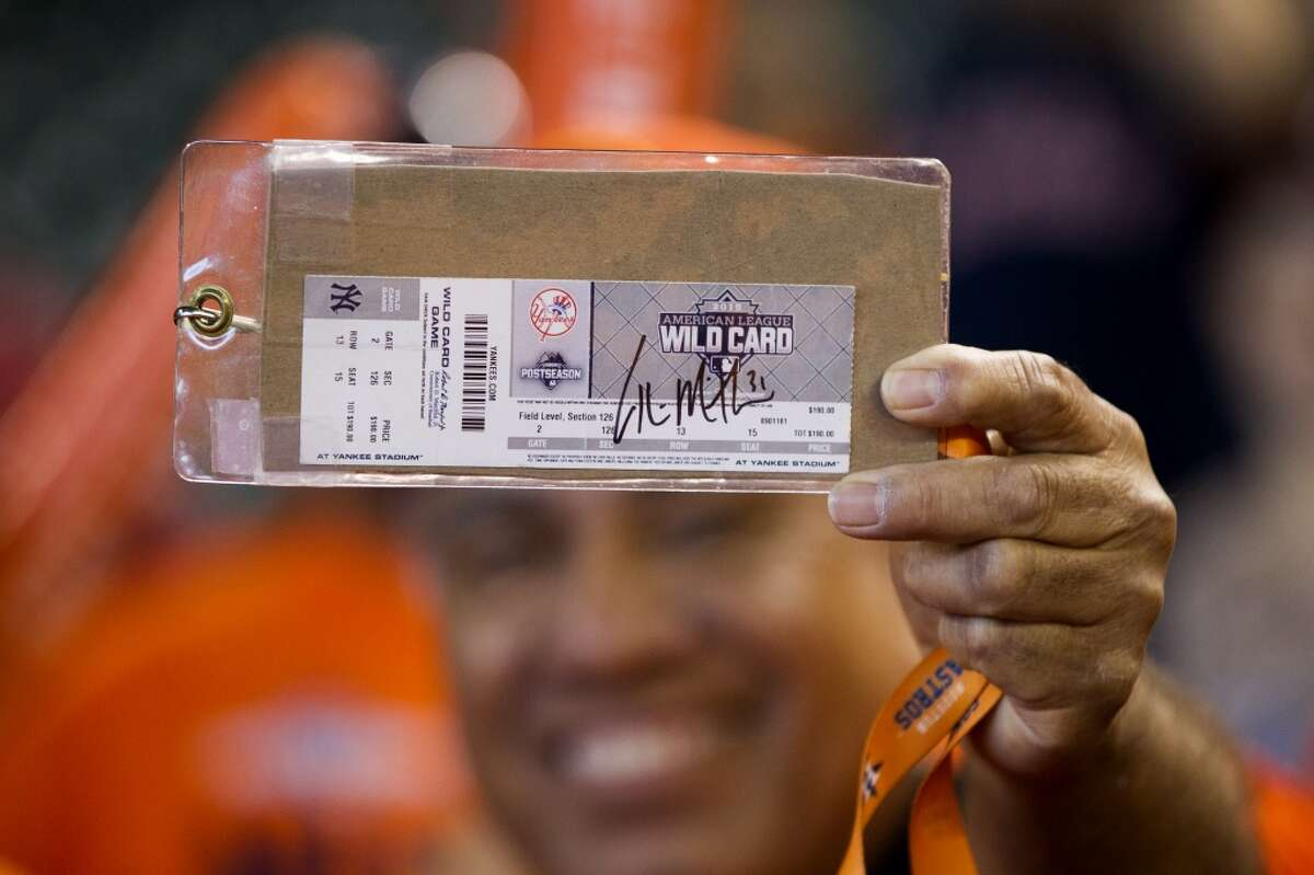 A Houston Astros fans holds up an American League Wild Card Game ticket before the American League Division Series Game 3 against the Kansas City Royals at Minute Maid Park on Sunday, Oct. 11, 2015, in Houston. ( Karen Warren / Houston Chronicle )
