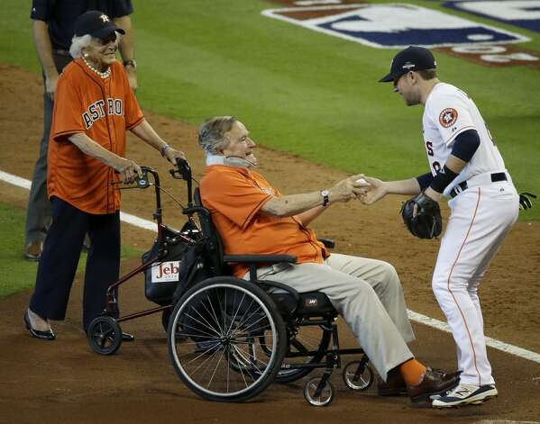 Barbara Bush, left, watches as former President George H.W. Bush has a ball sign by Houston Astros Jed Lowrie after throwing out the first pitch during pre-game ceremonies of Game 3 of the American League Division Series between the Houston Astros and Kansas City Royals at Minute Maid Park Sunday, Oct. 11, 2015, in Houston.  Photo: Houston Chronicle