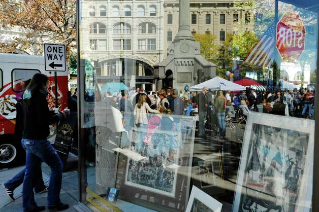 The scene of downtown Troy is reflected in the window of the Clement Frame and Art store during TroyOs Chowder Fest on Sunday, Oct. 11, 2015, in Troy, N.Y.  In its ninth year, this year featured 25 different homemade chowders from 19 different establishments.  (Paul Buckowski / Times Union) Photo: PAUL BUCKOWSKI / 10033662A