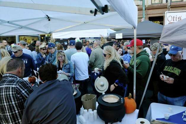 Workers with Russo's Grill, locations in Amsterdam, Broadalbin and Ballston Spa come November, dish out their seafood bisque chowder during TroyOs Chowder Fest on Sunday, Oct. 11, 2015, in Troy, N.Y.  In its ninth year, this year featured 25 different homemade chowders from 19 different establishments.  (Paul Buckowski / Times Union) Photo: PAUL BUCKOWSKI / 10033662A