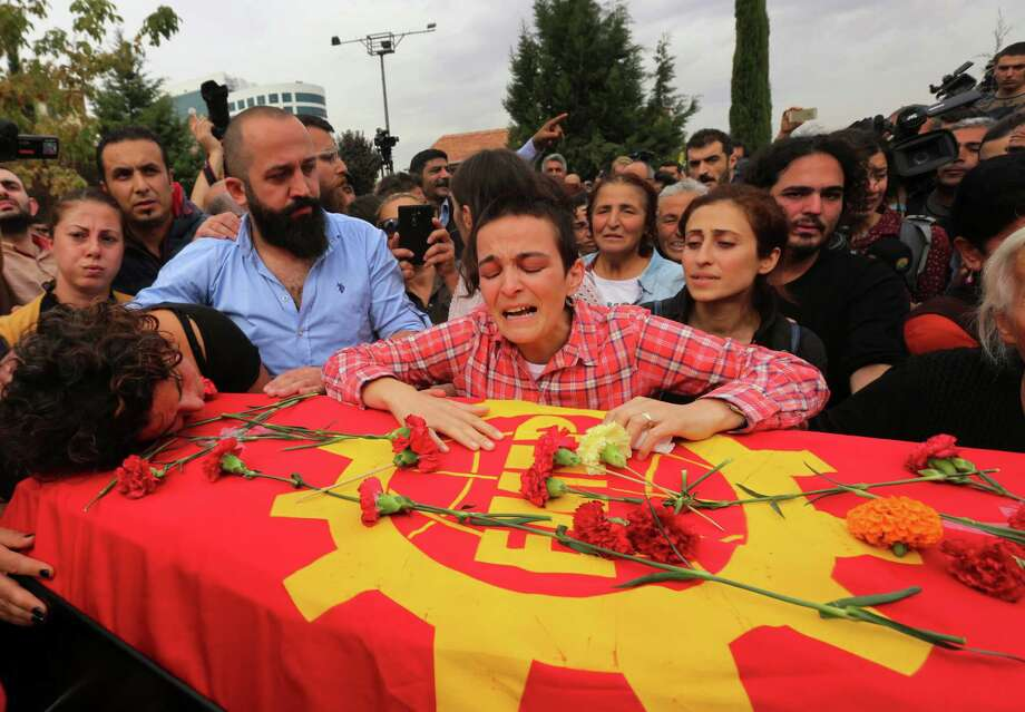 Relatives cry over the coffin of Korkmaz Tedik, 25, killed in Saturday's bombing attacks, during his funeral, at the Pir Sultan Abdal Cemevi, a place of worship for Turkey's Alevi community in the outskirts of Ankara, Turkey, Sunday, Oct. 11, 2015. Turkey declared three days of mourning following Saturday's nearly simultaneous explosions that targeted a peace rally in Ankara to call for increased democracy and an end to the renewed fighting between the Turkish security forces and Kurdish rebels. (AP Photo/Burhan Ozbilici) ORG XMIT: XLP125 Photo: Burhan Ozbilici / AP