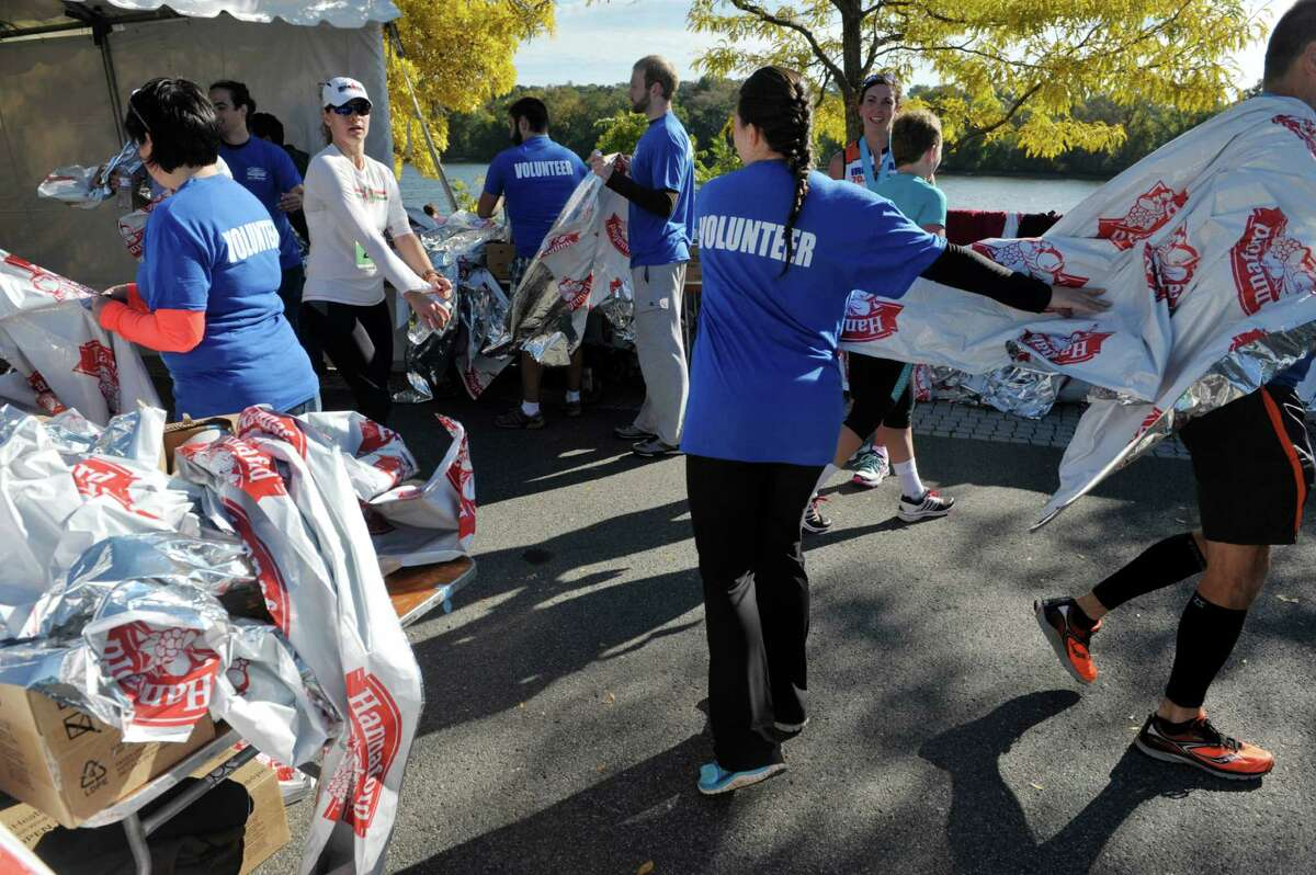 Volunteers pass out thermal mylar blankets to runners after they crossed the finish line during the Mohawk Hudson River Marathon and the Hannaford Half Marathon on Sunday, Oct. 11, 2015, in Albany, N.Y. (Paul Buckowski / Times Union)