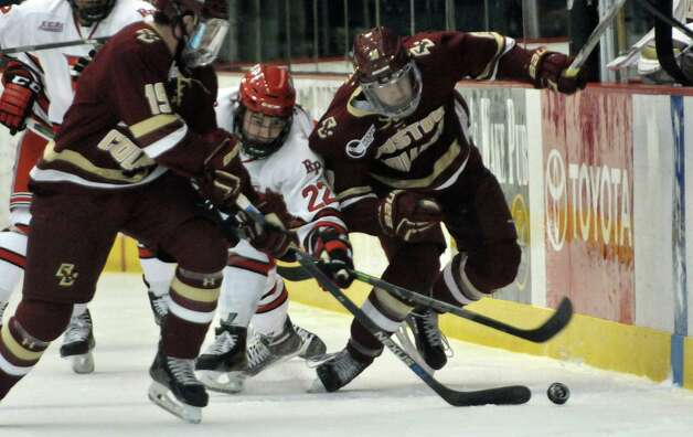 RPI's Bradley Bell, center, fights Boston College players for control of the puck during their game on Sunday, Oct. 11, 2015, in Troy, N.Y. (Paul Buckowski / Times Union) Photo: PAUL BUCKOWSKI / 10033671A