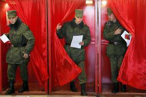 Belarusian army soldiers leave voting cabins at a polling station during presidential elections in Minsk, Belarus, Sunday, Oct. 11, 2015. (AP Photo/Dmitry Lovetsky)