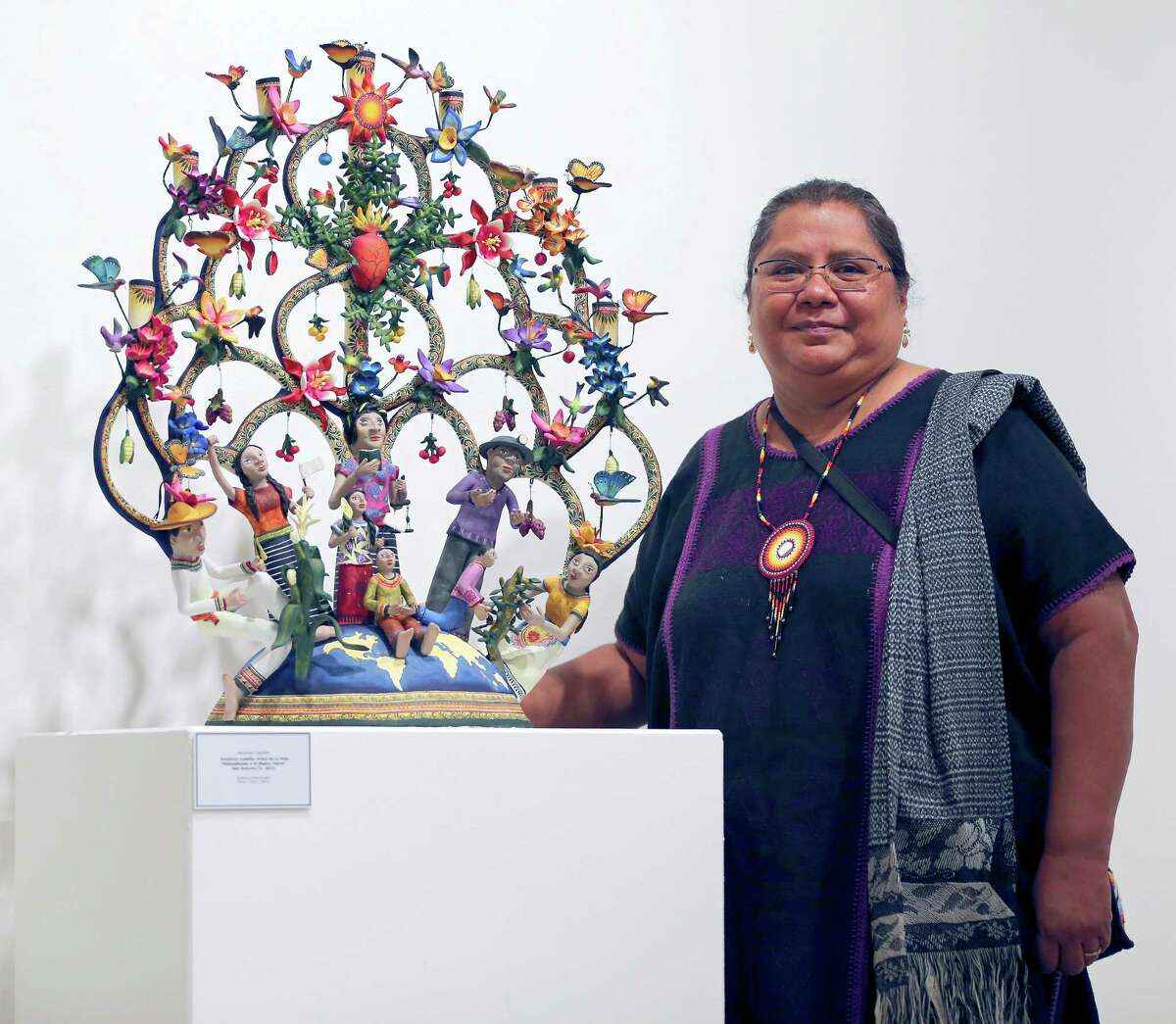 Veronica Castillo, a folk artist who was awarded an NEA National Heritage Fellowship in 2013 poses Oct. 6, 2015 next to one of her sculptures on display at the TAMU-SA Centro de Artes.