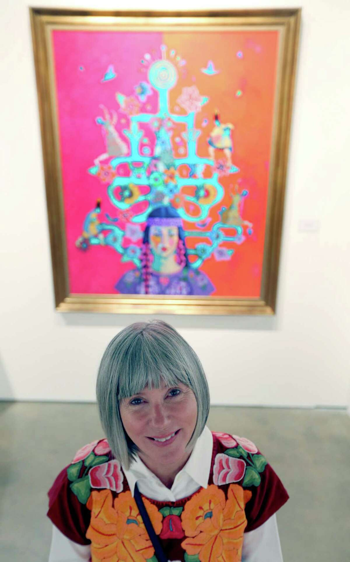 Kathy Sosa poses Oct. 6, 2015 in front of one of her paintings on display at the TAMU-SA Centro de Artes.