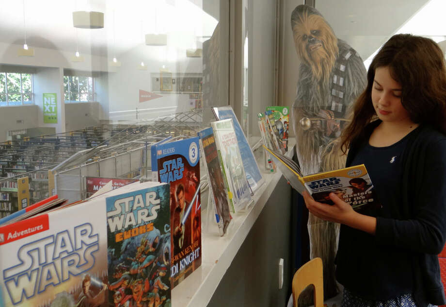 "Charlotte Harbottle, 12, of Westport, looks at one of the Star Wars books on display during Westport Library's ""Star Wars Reads"" program. Photo: Mike Lauterborn / For Hearst Connecticut Media / Westport News"