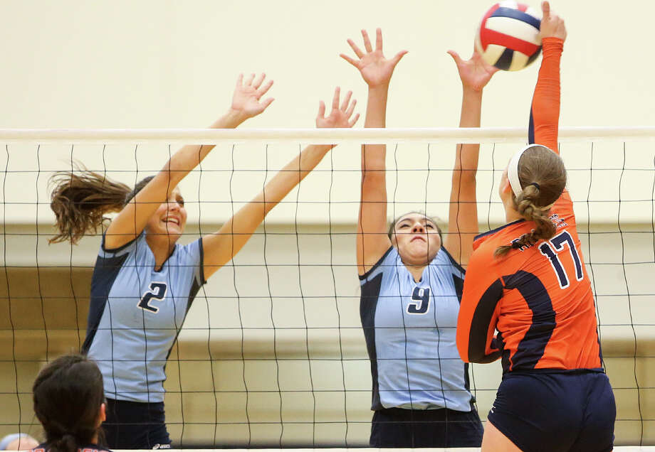 Johnson's Lauren Bault (top left) and Babriela Moran try to block a shot by Brandeis's Emily De Walt (right) during their season-opening match at Paul Taylor Field House on Monday, Aug. 10, 2015. Johnson won the match in four sets, 22-25, 25-13, 25-14, 28-26. Photo: Marvin Pfeiffer /San Antonio Express-News / Express-News 2015