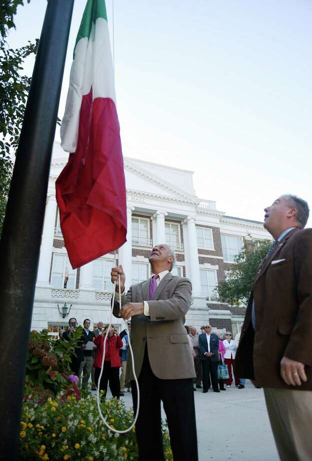 Samuel Telerico, left, and St. Lawrence Society President Tod Laudonia raise the Italian flag during the annual Columbus Day flag raising at Town Hall in Greenwich on Monday. Photo: Tyler Sizemore / Hearst Connecticut Media / Greenwich Time