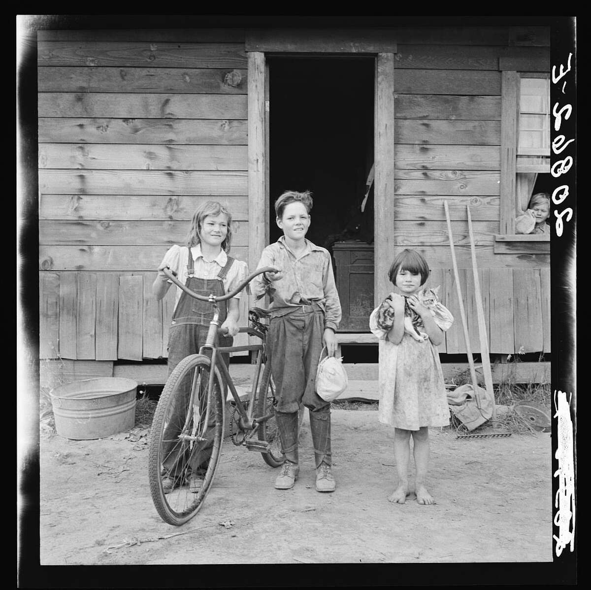Original caption: Three of the four Arnold children. The oldest boy earned the money to buy his bicycle. Western Washington, Thurston County, Michigan Hill. Photo by Dorothea Lange, August 1939.