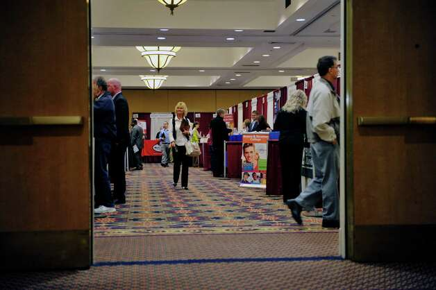 People make their way between booths for various businesses at the Times Union Job Fair on Monday, Oct. 12, 2015, in Colonie, N.Y.     (Paul Buckowski / Times Union) Photo: PAUL BUCKOWSKI / 10033723A