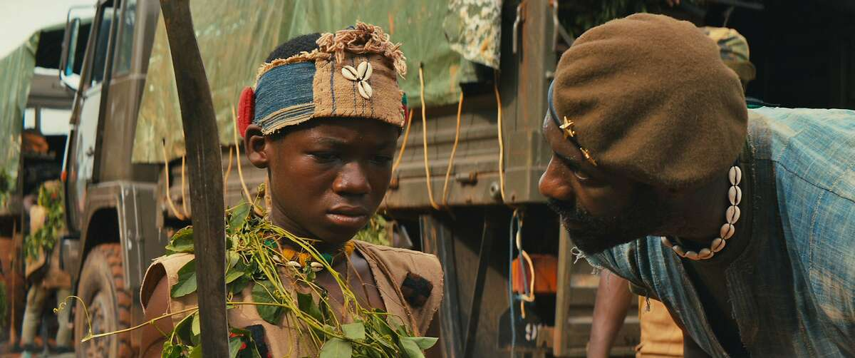 """This photo provided by Netflix shows, Abraham Attah, left, as Agu, and Idris Elba, as Commandant, in the Netflix original film, """"Beasts of No Nation,"""" directed by Cary Fukunaga. (Shawn Greene/Netflix via AP)"""