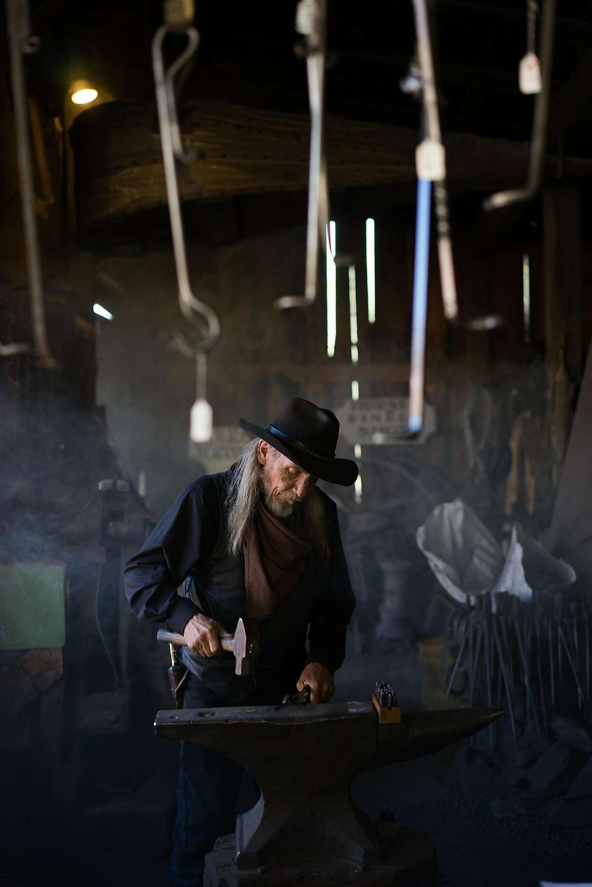 Mike Maciejewski hammers a small sword at the blacksmith shop at Columbia State Park in Columbia, Calif. on Friday, Oct. 9, 2015. Columbia has the largest number of gold rush-era buildings.