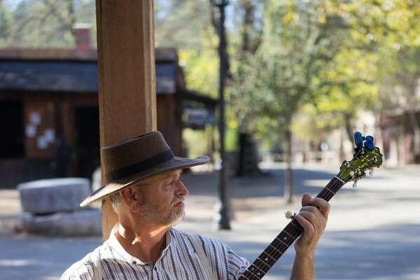Rick Walters plays the banjo at Columbia State Park in Columbia, Calif. on Friday, Oct. 9, 2015. Columbia has the largest number of gold rush-era buildings.