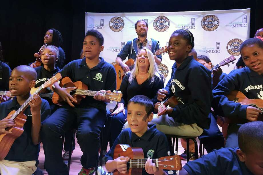 In this Oct. 5, 2015 photo, Liz Rose, center, a Grammy-award winning country music songwriter from Nashville, rehearses a song with students at Pelham Gardens Middle School in the Bronx borough of New York. Rose is working with the students through a program funded by the Country Music Association Foundation which provides a curriculum for teachers to develop language skills through the art of songwriting. (AP Photo/William Mathis) ORG XMIT: NYR401 Photo: William Mathis / William Mathis