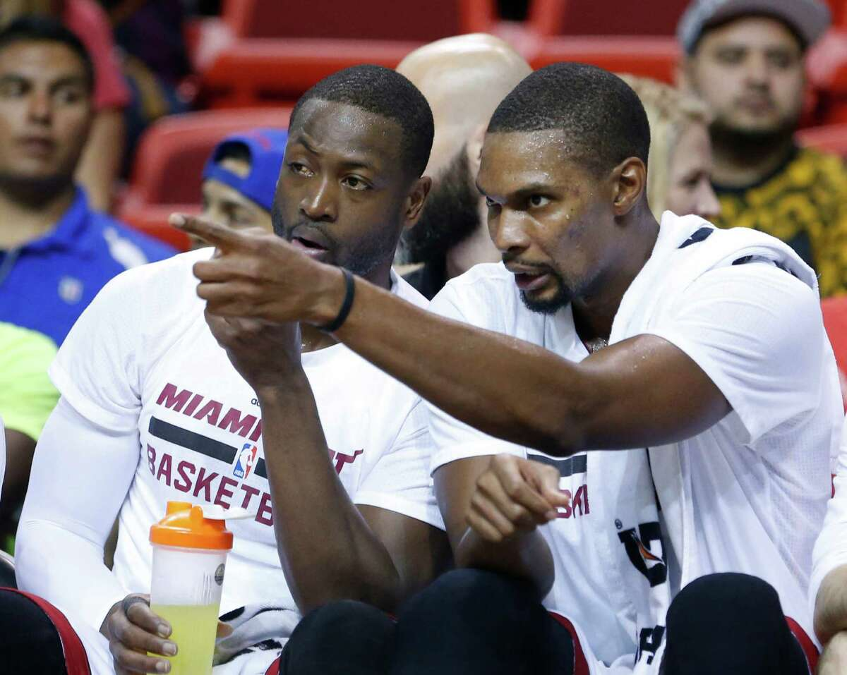Miami Heat guard Dwyane Wade, left, and forward Chris Bosh chat as they rest on the bench during the first half of a preseason NBA basketball game against the San Antonio Spurs, Monday, Oct. 12, 2015, in Miami. (AP Photo/Wilfredo Lee)