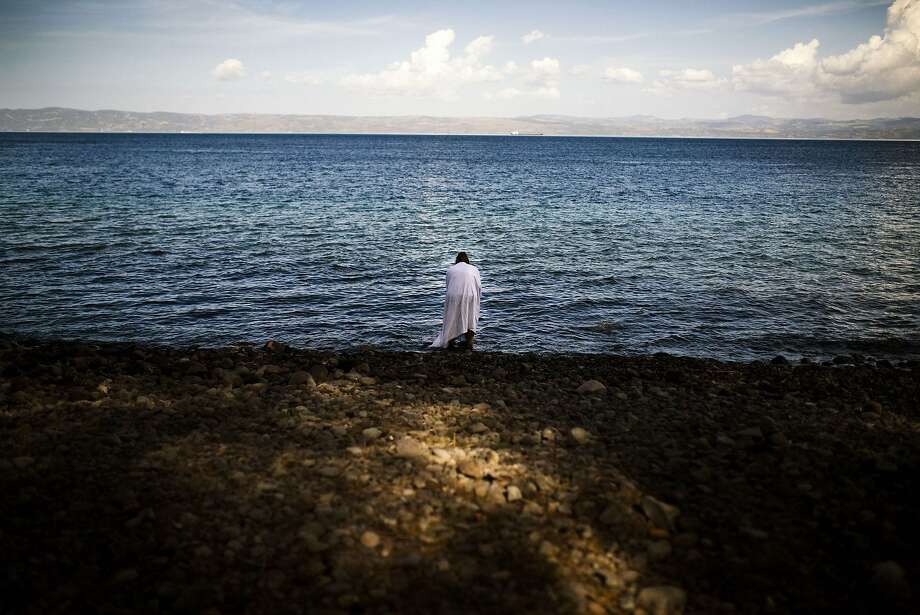 A woman stands on the beach, shortly after she arrived on the Greek island of Lesbos after crossing the Aegean sea from Turkey on October 12, 2015. Greece was hit by a huge new surge in migrants as the United Nations on October 9 approved a European seize-and-destroy military operation against people smugglers in the Mediterranean. Photo: Dimitar Dilkoff, AFP / Getty Images