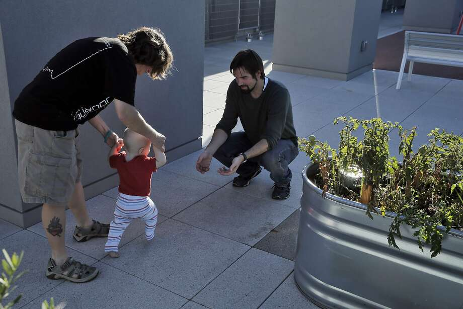 Danielle Williams holds her son Liam, 9 mos., as he walks to Kyle Golden, the Intensive Case Manager, after they tended to the public garden at the Sansom Broadway Apartments, part of the Chinatown Community Development Center, in San Francisco, Calif., on Monday, October 12, 2015. The CCDC was built on surplus city property and Proposition K on the November ballot would make city departments to come up with a list of unused property and allocate it for housing needs. Photo: Carlos Avila Gonzalez, The Chronicle