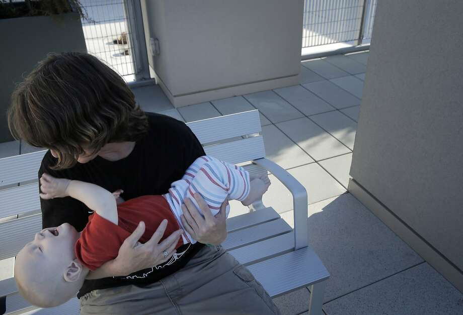 Danielle Williams holds her son Liam, 9 mos., after she tended to the rooftop tenant garden at the Sansom Broadway Apartments, part of the Chinatown Community Development Center, in San Francisco, Calif., on Monday, October 12, 2015. The CCDC was built on surplus city property and Proposition K on the November ballot would make city departments to come up with a list of unused property and allocate it for housing needs. Photo: Carlos Avila Gonzalez, The Chronicle