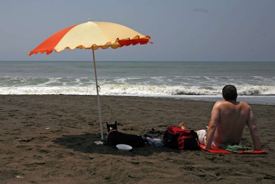 "In this file photo, Darin Severns, of San Francisco, enjoys warm temperatures with his Boston terrier ""Minnie"" the Pacifica Pier. High temps were expected across the Bay Area Monday as a stubborn ridge of high pressure parked itself over the region. Photo: Kim Komenich, The Chronicle"