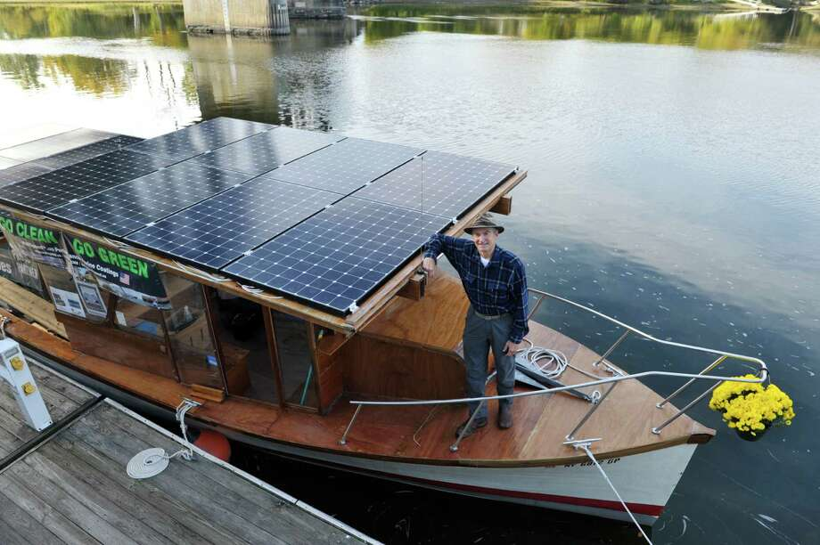 David Borton, captain of the  boat Solar Sal, stands on his baot at the Waterford Harbor Front on Tuesday, Oct. 13, 2015, in Waterford, N.Y.  Solar Sal, began the first ever cargo delivery in the history of the Erie Canal done entirely without fossil fuels in Lockport on September 29th.  The boat is powered solar panels.  Solar Sal is carrying four tons of cardboard for recycling bound for Cascades' Mechanicville plant.  The boat made a stop in Waterford before heading up to Mechanicville for its final stop and to deliver the cargo.  (Paul Buckowski / Times Union) Photo: PAUL BUCKOWSKI / 10033726A
