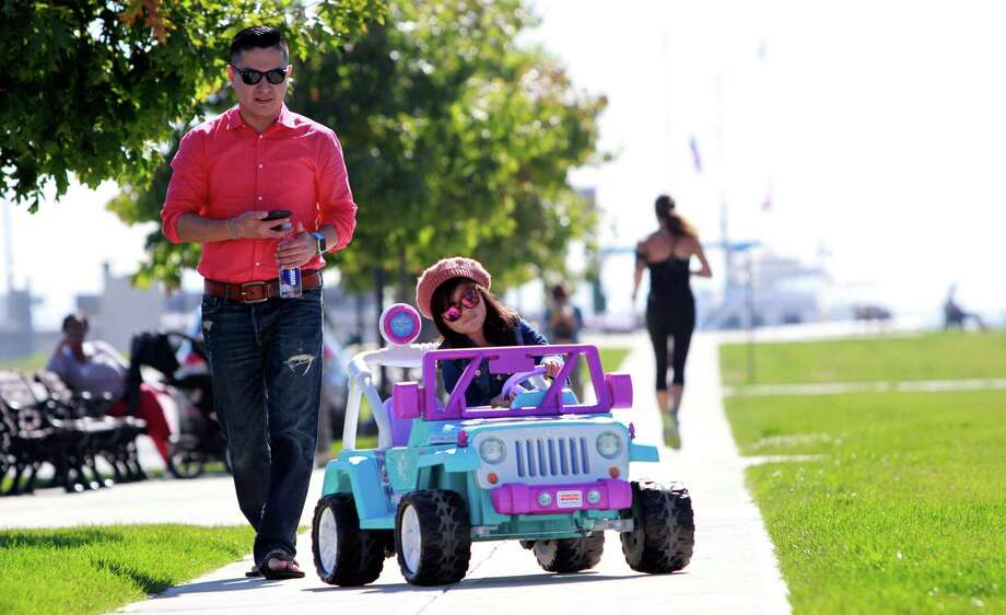 Allyson Angeles, 4, of Stamford, enjoys a drive at Harbor Point a her father, Walter, follows close behind. The two were enjoying the warm fall weather. Photo: Matthew Brown / For Hearst Connecticut Media / Connecticut Post Freelance