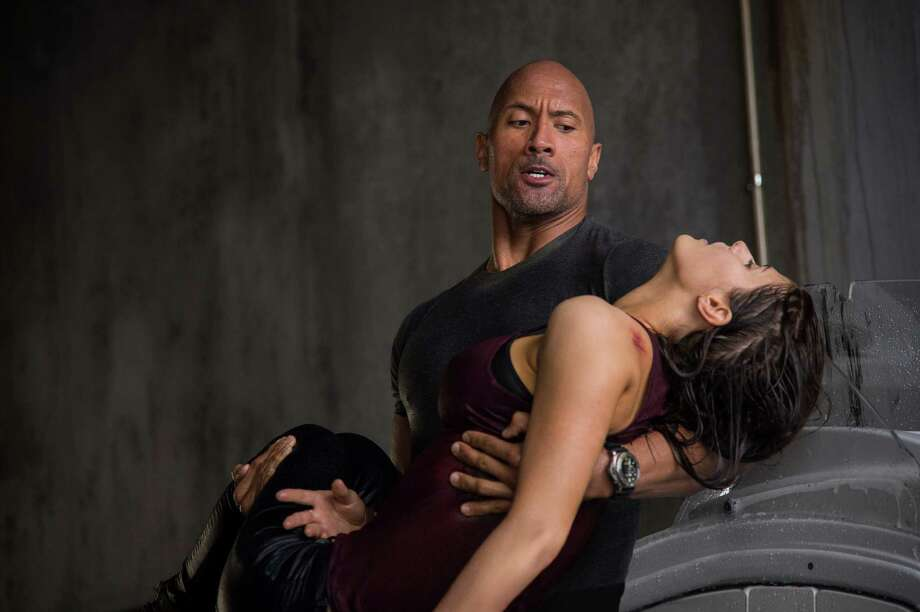 "Dwayne Johnson, left, rescues Carla Gugino from a pile of rubble that used to be Los Angeles in ""San Andreas."" Photo: Warner Bros. Pictures / Warner Bros. Pictures"
