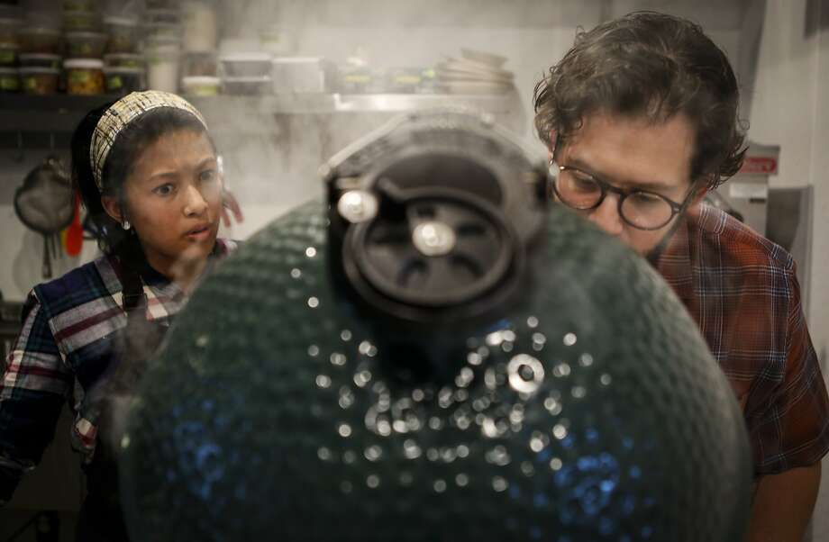 Matthew Lightner works with cook Monica Feybesse to get coals to the correct temperature in a Big Green Egg at his new restaurant, Ninebark. Photo: Russell Yip, The Chronicle