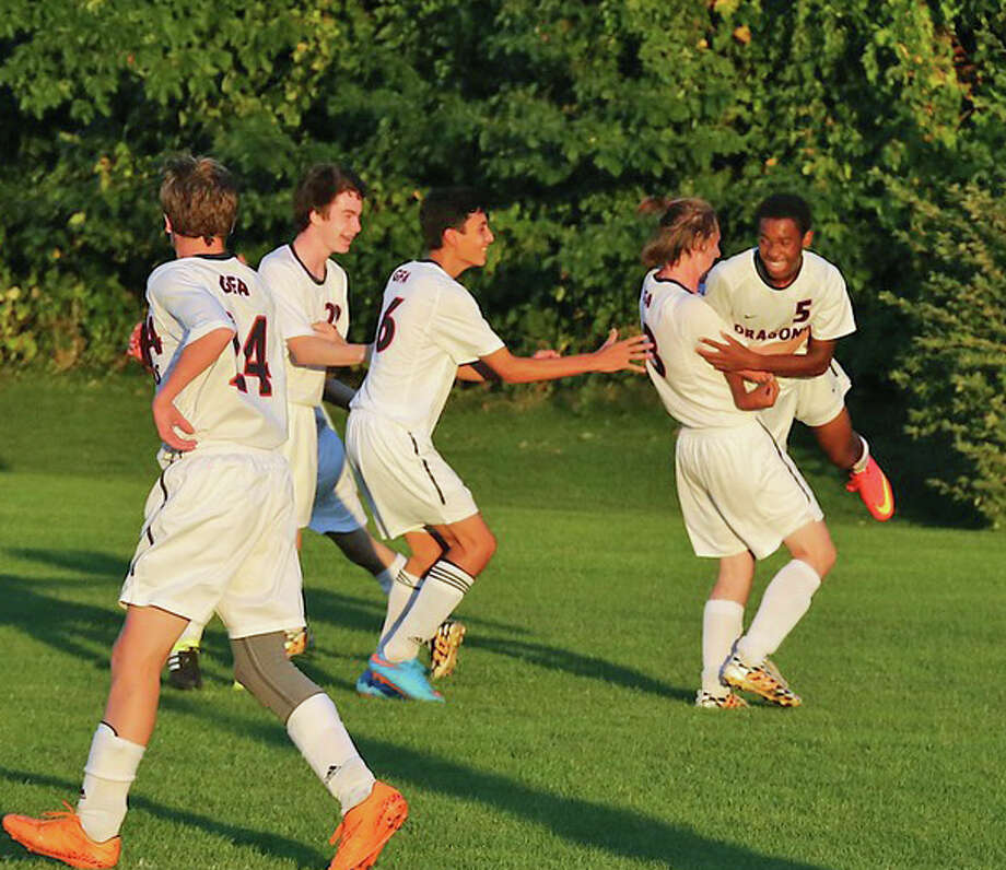 GFA boys soccer teammates Zach Liston (No. 22), James Velgot (No. 26) and Patrick Friend congratulate Nick  Attai, right, on his first goal of the season. GFA beat Hamden Hall Wednesday, Oct. 7, by a score of 6-1. Photo: Contributed Photo / Westport News Contributed