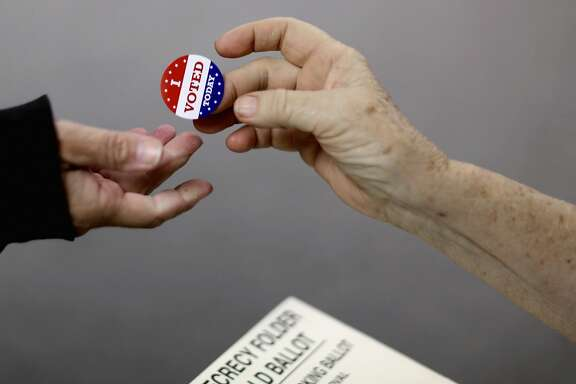 RED OAK, IA - NOVEMBER 04:  (ONE OF A 70-PICTURE PACKAGE)   Voters get an 'I VOTED TODAY' sticker after casting their ballots on election day at the Red Oak Fire Department November 4, 2014 in Red Oak, Iowa. According to the polls, Republican U.S. Senate candidate Joni Ernst is in a neck-and-neck race with Democratic candidate Rep. Bruce Braley (D-IA), and the election in Iowa could decide which party controls the U.S. Senate.  (Photo by Chip Somodevilla/Getty Images)