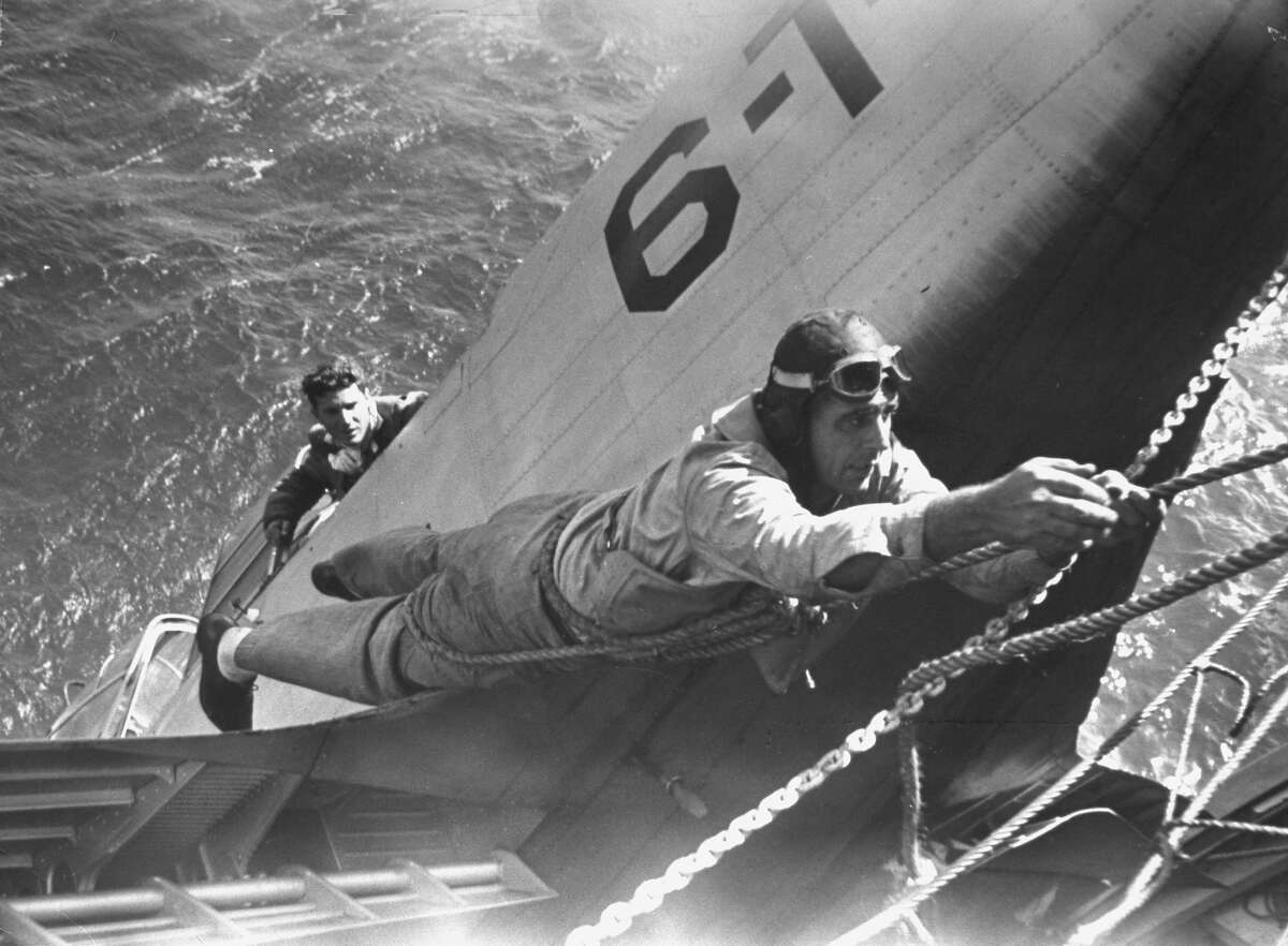 A Navy pilot being rescued from plane hanging over side of an aircraft carrier in 1940. Take a look at more historical images of the Navy in this slideshow.