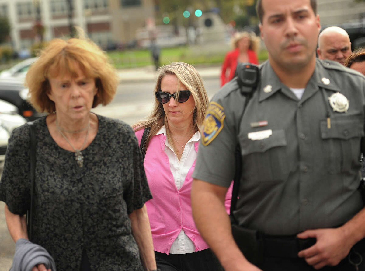 Jennifer Connell, center, is escorted to her car by marshals after a state Superior Court jury decided against her in her lawsuit against her 12-year-old Westport nephew She sued her nephew, who was 8 at the time of the incident, for breaking her wrist after exuberantly jumping into her arms after she arrived at an event.