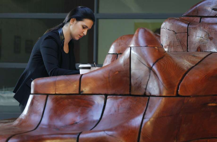 Art graduate student Alexandria Brown studies at a large desk carved from wood in the courtyard at the McMurtry Building. Photo: Paul Chinn, The Chronicle