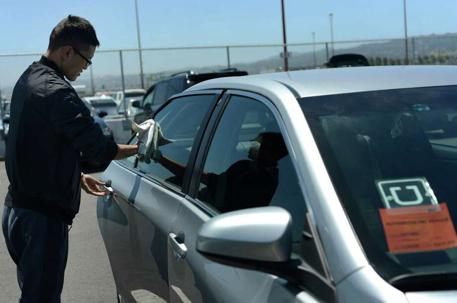 Uber driver Idertsog Darhkan, 23, cleans his car in a parking lot near San Francisco International Airport in June. Some disgruntled UberX drivers and ex-drivers plan to refrain from working this weekend. Photo: Brandon Chew / Brandon Chew / The Chronicle / ONLINE_YES