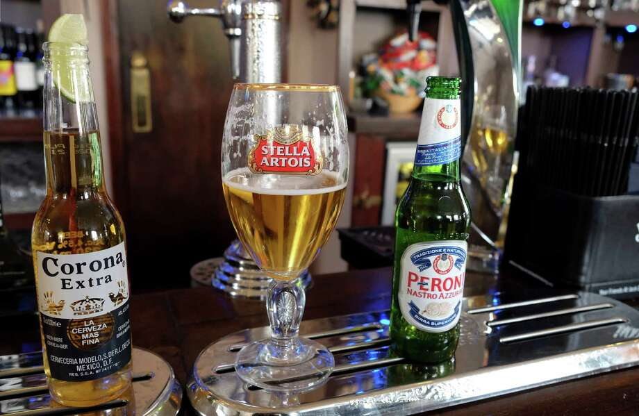 Drinks sit on the bar in a pub in London, Tuesday, Oct. 13, 2015. The world's top two beer makers agreed Tuesday to join forces to create a company that would control nearly a third of the global market. AB InBev's brands include Budweiser, Stella Artois and Corona, while SABMiller produces Peroni and Grolsch. (AP Photo/Kirsty Wigglesworth) ORG XMIT: LKW103 Photo: Kirsty Wigglesworth / AP
