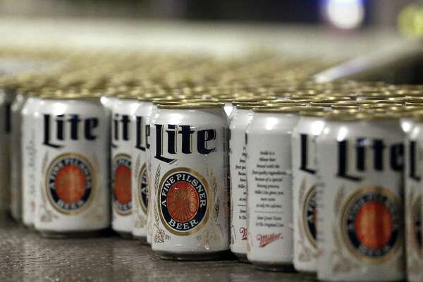 In this March 11, 2015 photo, newly-filled and sealed cans of Miller Lite beer move along on a conveyor belt, at the MillerCoors Brewery, in Golden, Colo. After turning down five offers, British-based brewer SABMiller, which sells beers including Miller Lite, Coors Light and Blue Moon in the U.S. and Puerto Rico through a joint venture with Molson Coors, on Tuesday, Oct. 13, 2015 accepted in principle an improved takeover bid worth 69 billion pounds ($106 billion) from Anheuser Busch InBev. Many analysts think that the merged company will be compelled to sell the Miller line of beers in the U.S. (AP Photo/Brennan Linsley) ORG XMIT: NYBZ192