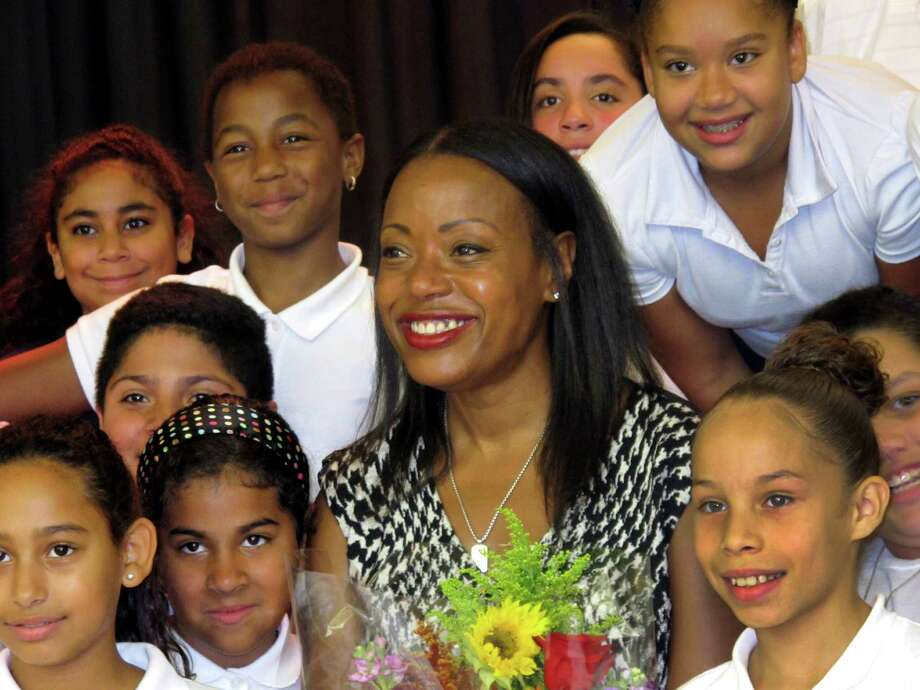 Fashion designer Tracy Reese poses with students at Barnum School in Bridgeport, Conn. on Tuesday, Oct 13, 2015. The visit was part of theTurnaround Arts program, a signature program of the President's Committee on Arts and the Humanities. Reese will spend the year visiting Barnum School and working with students to infuse arts into the curriculum. Photo: Linda Conner Lambeck / Hearst Connecticut Media / Connecticut Post