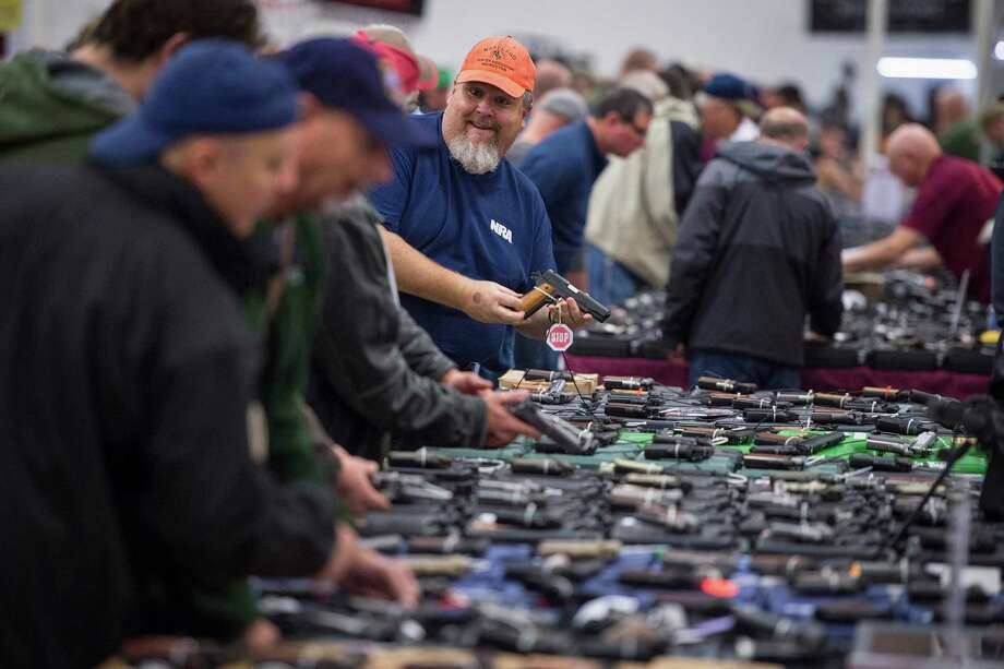 Gun enthusiasts look over some of the thousands of handguns offered by vendors at a gun show in Chantilly, Virginia. A reader says strict gun laws will not prevent criminals from getting firearms if they want them. Photo: Jabin Botsford /Washington Post / The Washington Post